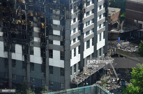 A firefighter protects himself with a riot shield as he enters the burning 24 storey residential Grenfell Tower block in Latimer Road West London on...