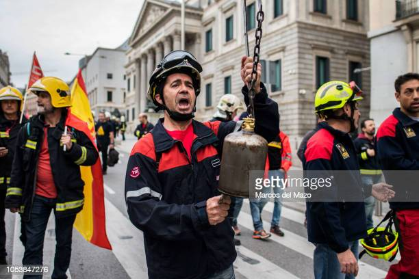 "Firefighter protests ringing a bell as he passes by the Congress of Deputies during a demonstration demanding a ""firefighters law"" and better working..."