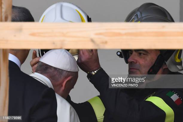 A firefighter puts a safety helmet on the head of Pope Francis as he arrives to the cathedral of Camerino as part of a visit on June 16 2019 to the...