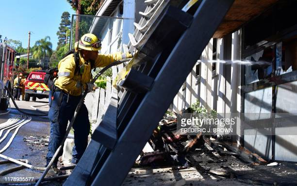 A firefighter puts out burning embers through broken glass at a home on North Tigertail Road near the Getty Center in Los Angeles California on...