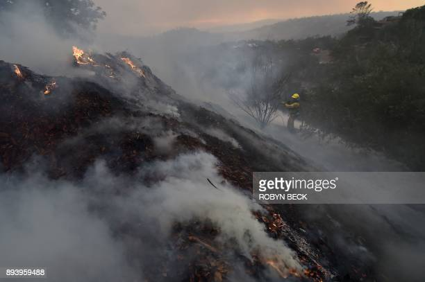 TOPSHOT A firefighter puts out hotspots on a smoldering hillside in Montecito California as strong winds blow smoke and embers inland December 16...