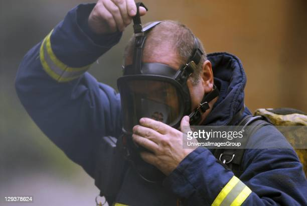 Firefighter putting on gas mask