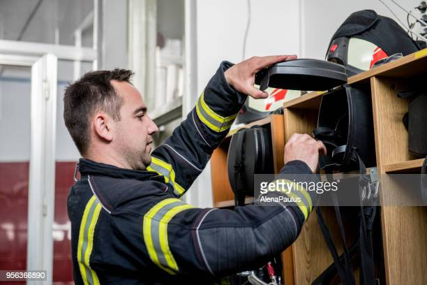 firefighter putting on gas mask - fire station stock photos and pictures