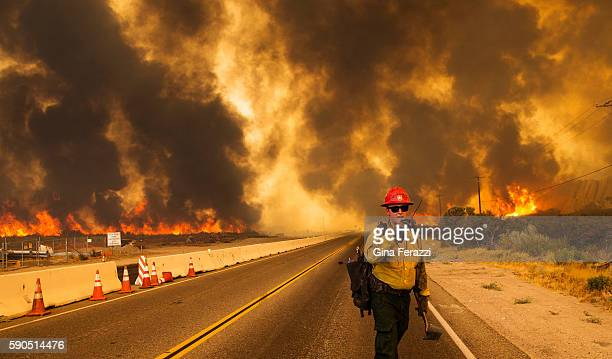 A firefighter radios that the Blue Cut Fire is burning on both sides of Highway 138 on August 16 2016 in Phelan California