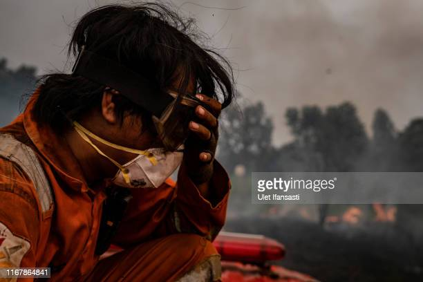 A firefighter reacts as they extinguish the fire on burned peatland and fields on September 13 2019 in Pulang Pisau regency Central Kalimantan...