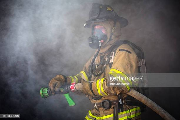 firefighter ready to spray water - extinguishing stock pictures, royalty-free photos & images