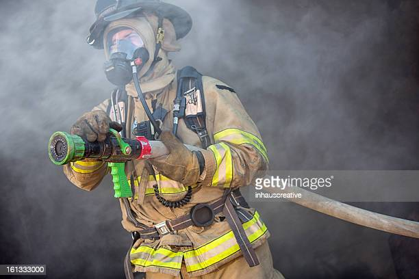 firefighter ready to spray water - firefighter stock pictures, royalty-free photos & images