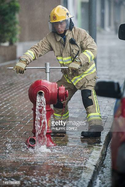 A firefighter releases pressure from a fire hydrant in the aftermath of Typhoon Vicente in Hong Kong on July 24 2012 More than 100 people were...