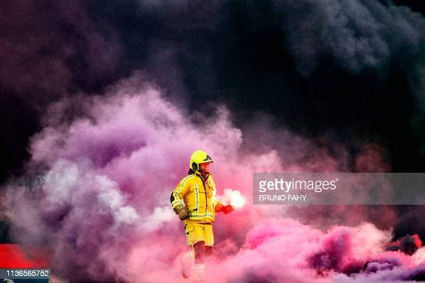 "Firefighter removes a flare as red smoke billows from the pitch during the Play-off 1 on day 4 of the ""Jupiler Pro League"" Belgian championship..."