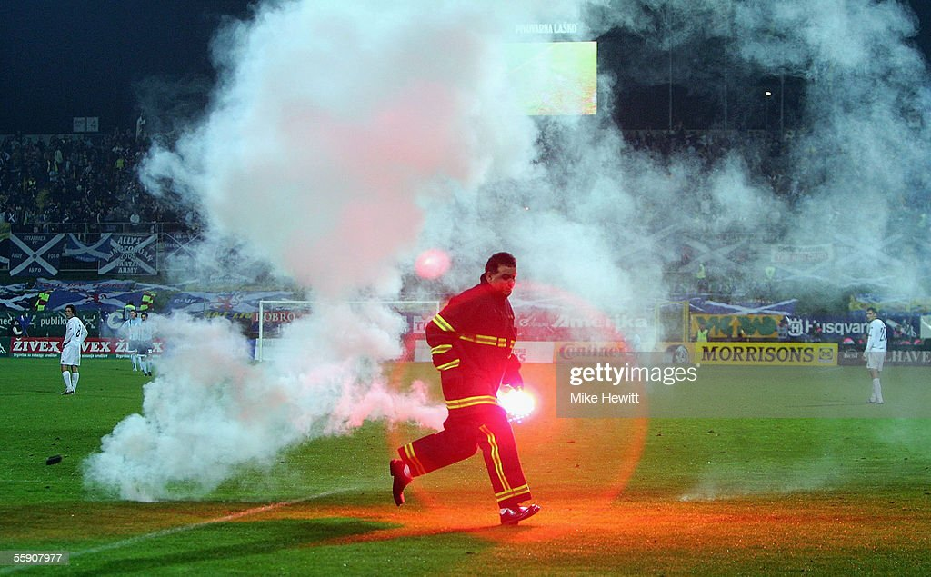 A firefighter removes a flare from the pitch during the FIFA World Cup group 5 qualifying match between Slovenia and Scotland on October 12, 2005 at the Petrol Arena Stadium in Celje, Slovenia.