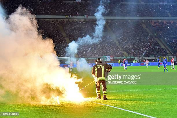 A firefighter removes flares thrown by football fans on the pitch during the Euro 2016 qualifying football match Italy vs Croatia on November 16 2014...