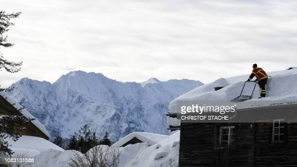 Firefighter removes snow from a rooftop in the small Bavarian village of Kruen near Garmisch-Partenkirchen, southern Germany, on January 15, 2019.