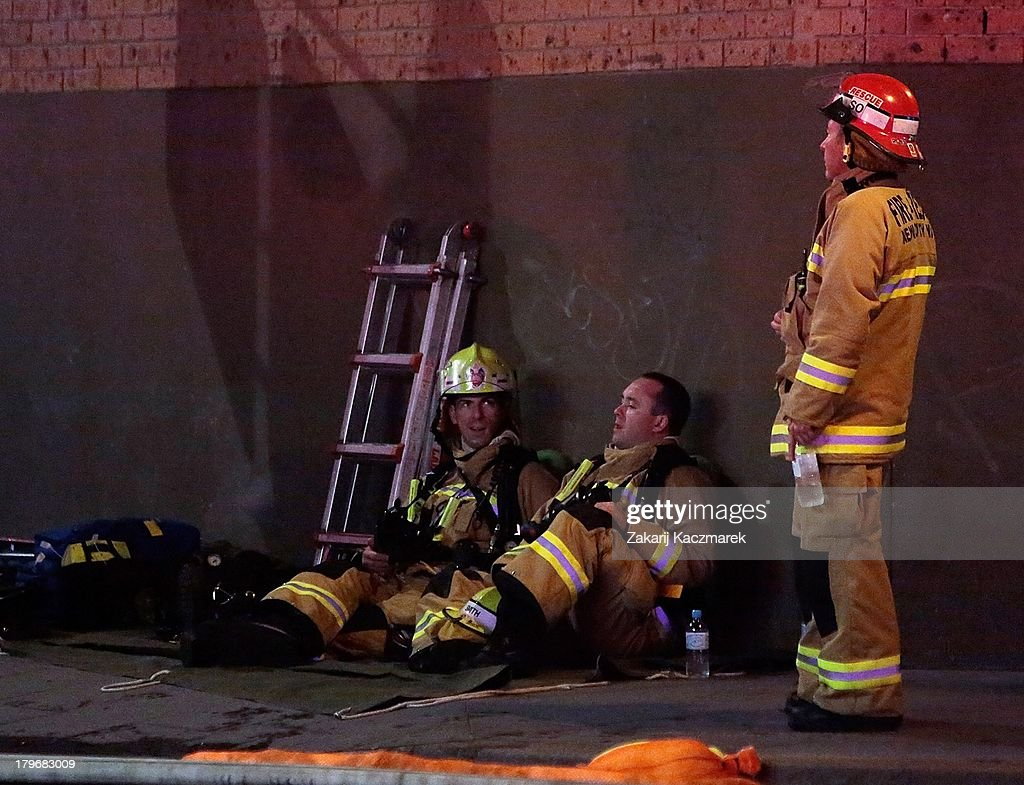 Firefighter rest after efforts to bring a fire under control in O'Connor Street, Chippendale, a mixed residential and commercial area, on September 6, 2013 in Sydney, Australia.
