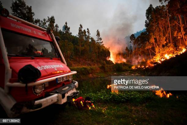 TOPSHOT A firefighter rests next to fire combat truck during a wildfire at Penela Coimbra central Portugal on June 18 2017 A wildfire in central...