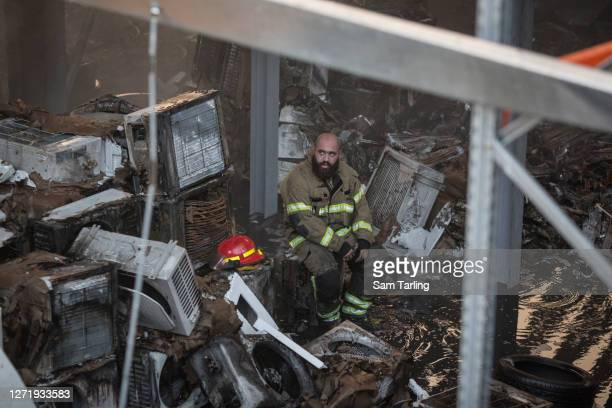 Firefighter rests on the charred remains of air conditioning units in a warehouse after a huge blaze at Beirut port on September 10, 2020 in Beirut,...