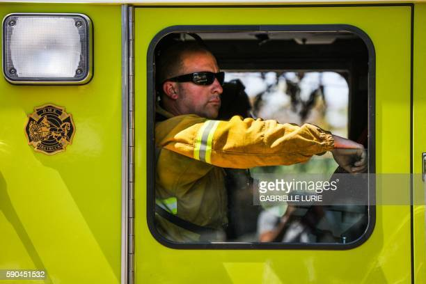 A firefighter rides in a firetruck while looking for power lines that were down after the Clayton Fire in Lower Lake California August 16 2016 A man...