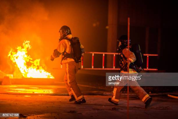 firefighter running - fire protection suit stock photos and pictures