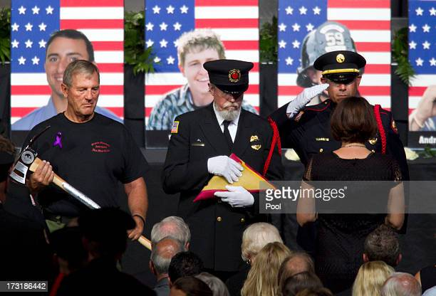 A firefighter salutes a family member of one of the fallen firefighters after presenting her with the American flag as two other firefighters wait to...