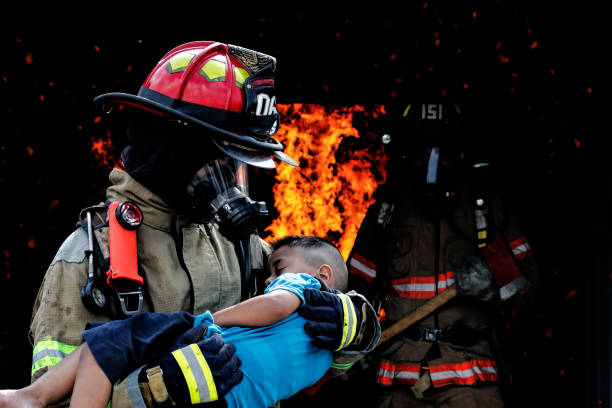 Firefighter saves a child from the fire. Fire prevention and extinguishing concept.