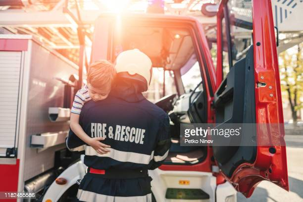 firefighter saving little boy - rescue services occupation stock pictures, royalty-free photos & images