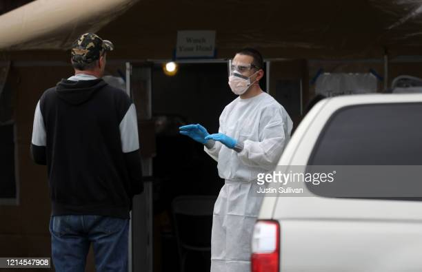 A firefighter screens a man that is waiting in line to get a COVID19 test at a free public testing station on March 24 2020 in Hayward California...