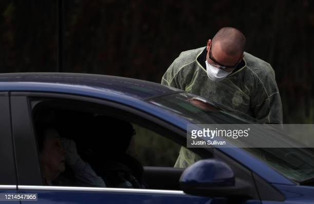 A firefighter screens people in a car that are waiting in line to get a COVID19 test at a free public testing station on March 24 2020 in Hayward...