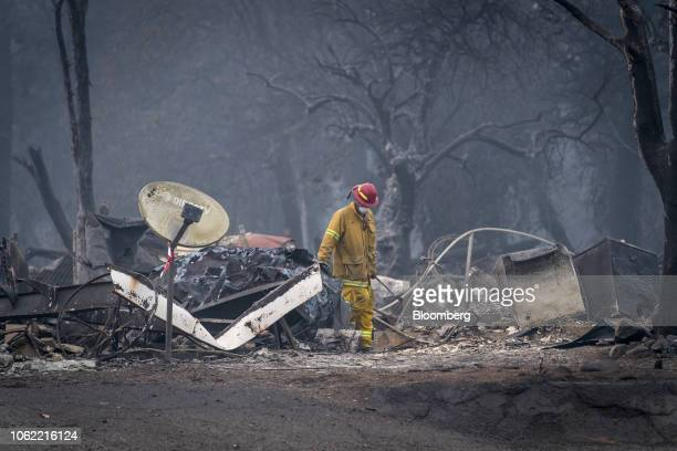 A firefighter searches a burnedout building in Paradise California US on Thursday Nov 15 2018 The number of acres burned in the blazes including the...