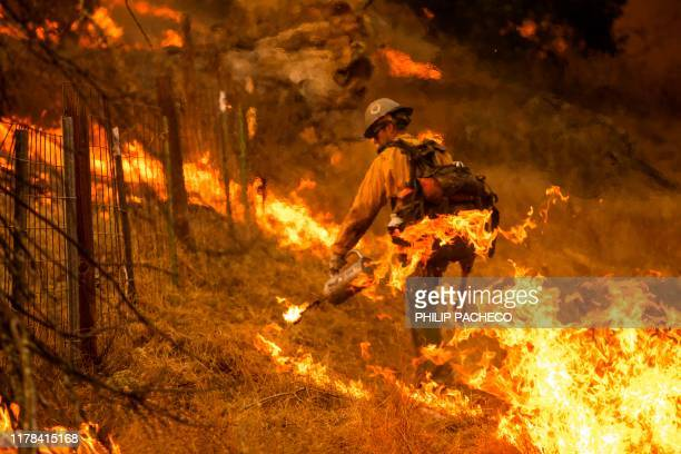 A firefighter sets a back fire along a hillside during firefighting operations to battle the Kincade Fire in Healdsburg California on October 26 2019...
