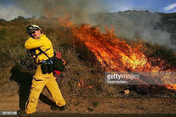 A firefighter shields his face from the heat of a backfire he is setting along State Route 241 toll road to fight an offseason wildfire in the...