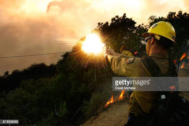 A firefighter shoots a flare gun into the brush as US Forest Service Hot Shots set a backfire to try to contain the Gap fire officially the top...