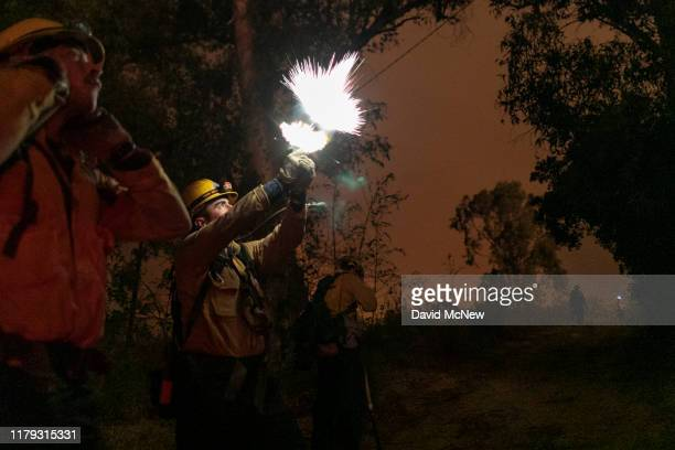 A firefighter shoots a flare gun to start a backfire at the Maria Fire which exploded to 8000 acres on its first night on November 1 2019 near Somis...