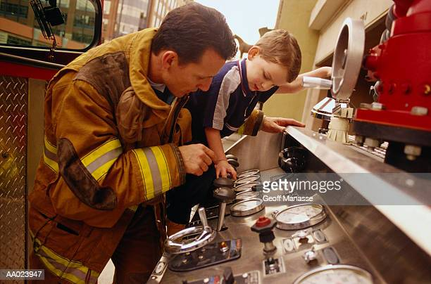 firefighter showing boy controls on a fire engine - fire station - fotografias e filmes do acervo