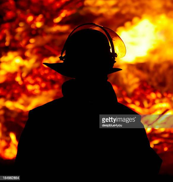 Firefighter silhouette against glowing fire