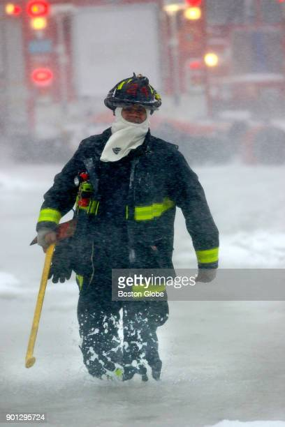 A firefighter sloshes through a high tide on Atlantic Avenue as a major snow storm hits Boston on Jan 4 2018