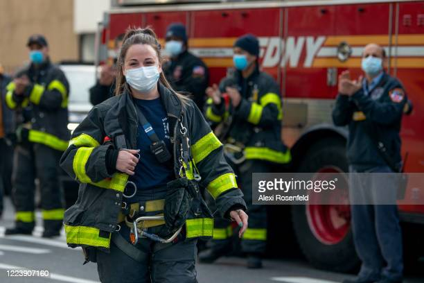 A firefighter smiles while walking towards a medical worker outside of NYU Langone Health hospital during the nightly 'Clap Because We Care' cheer...