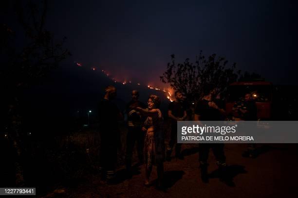 Firefighter speak to villagers as a wildfire burns in Vale da Cuba near Isna village, Castelo Branco, on July 26, 2020.