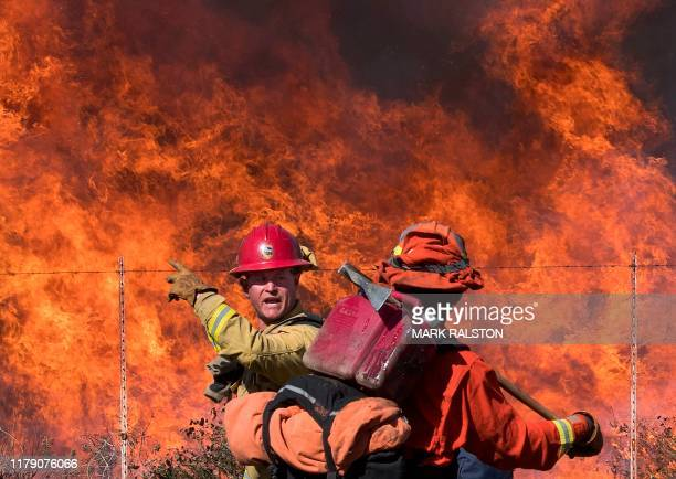 A firefighter speaks to an inmate firefighter as they prepare to put out flames on the road leading to the Reagan Library during the Easy Fire in...