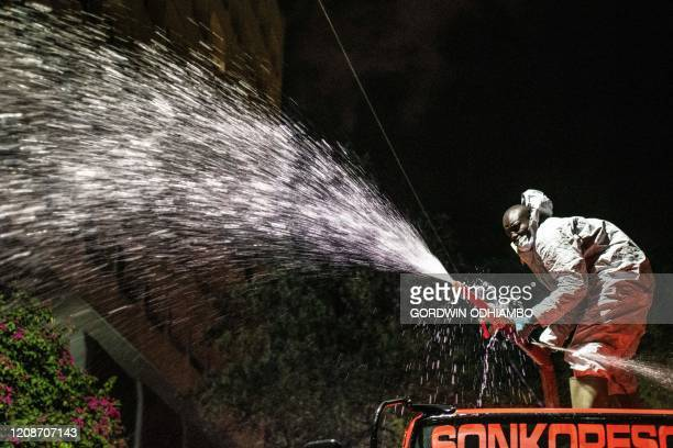 A firefighter spray disinfectant on a street during the night curfew to curb the spread of the COVID19 coronavirus in Nairobi Kenya on March 30 2020...