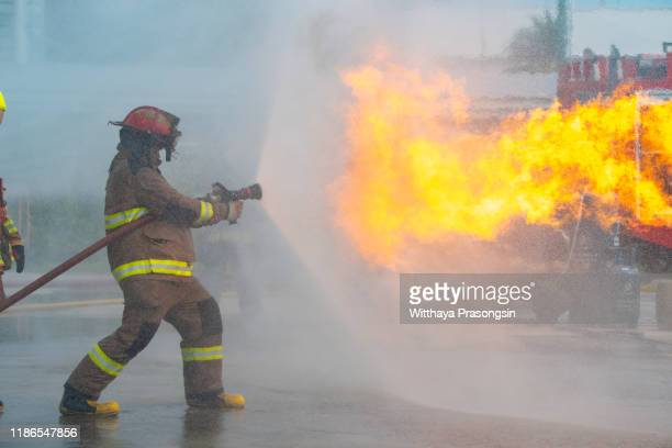 firefighter spraying water at a house fire - extinguishing stock pictures, royalty-free photos & images