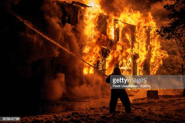 firefighter spraying water on burning fire at night - inferno stock photos and pictures