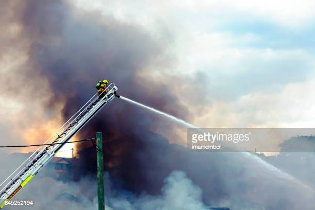 Firefighter spraying water on burning house, background with copy space