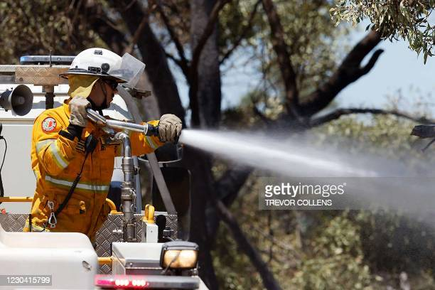 Firefighter sprays a hose from his truck to put out spot fires while battling a bush fire in Kwinana, some 30 kilometres south of Perth on January 4,...