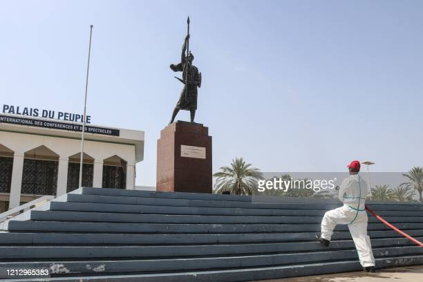 Firefighter sprays disinfectant on the statue of the warrior of independence in front of the People's Palace, a public ceremony hall, in Djibouti, on...