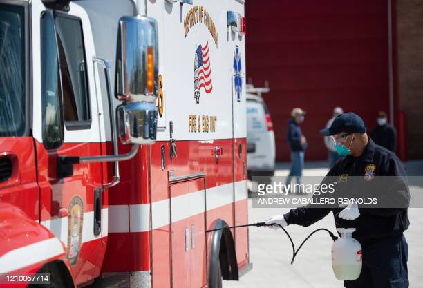 A firefighter sprays disinfectent on an ambulance before it enters a facility for decontamination after it was exposed to a suspected COVID19 case at...