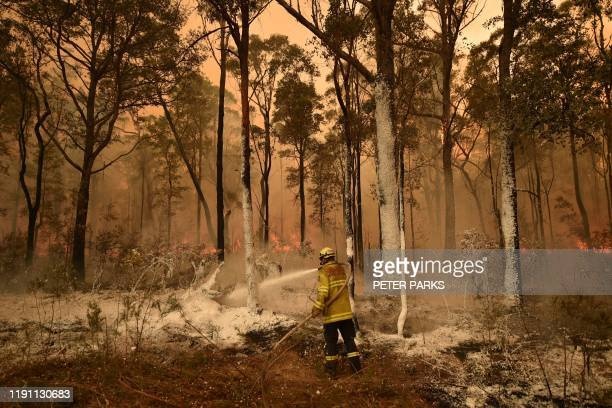 TOPSHOT A firefighter sprays foam retardant on a back burn ahead of a fire front in the New South Wales town of Jerrawangala on January 1 2020 A...
