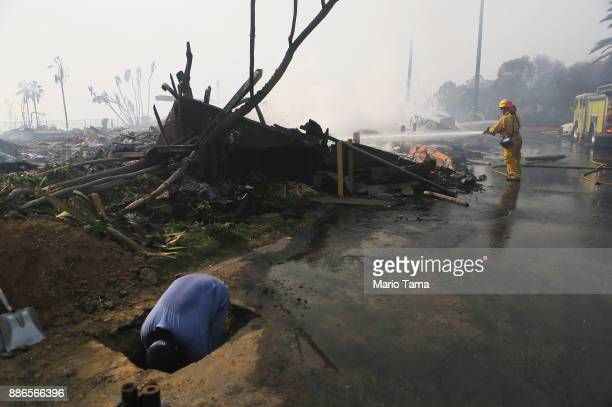 A firefighter sprays water as gas worker operates at the remains of an apartment complex destroyed by the Thomas Fire on December 5 2017 in Ventura...