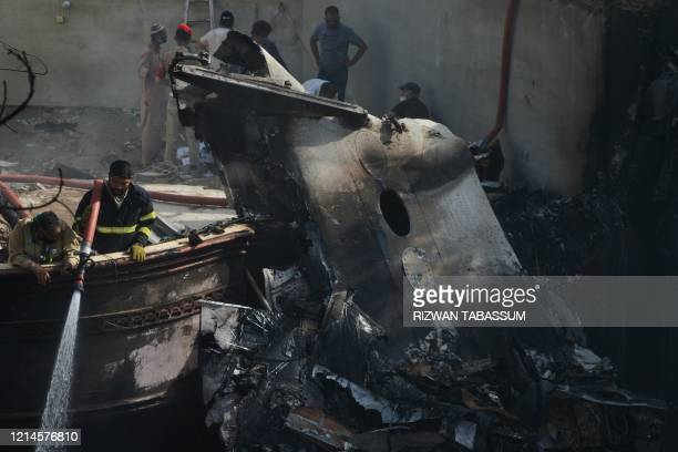 TOPSHOT A firefighter sprays water on the wreckage of a Pakistan International Airlines aircraft after it crashed in a residential area in Karachi on...