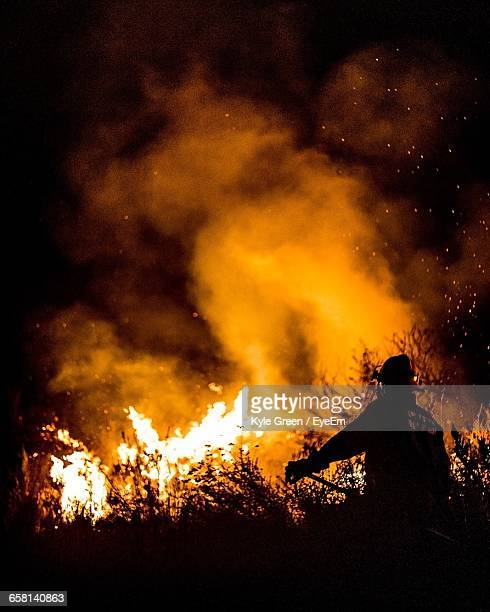 Firefighter Standing Against Fire In Forest At Night