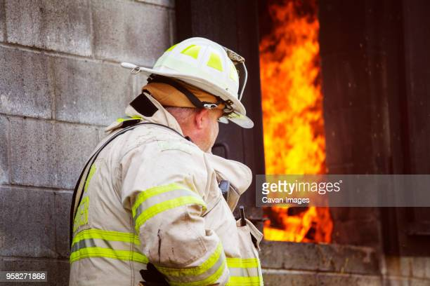 Firefighter standing by wall