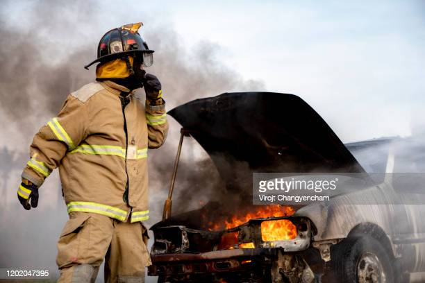 firefighter standing in front of a burned car - rescue worker stock pictures, royalty-free photos & images